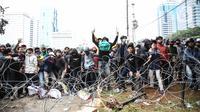 Pengunjuk rasa berupaya menerobos barikade polisi di kawasan Patung Kuda, Jakarta Pusat, Selasa (13/10/2020). Bentrokan antara massa aksi menolak UU Cipta Kerja dan kepolisian pecah. (Liputan6.com/Faizal Fanani)