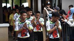 12 anak laki-laki dan pelatih sepak bola mereka, yang diselamatkan dari gua banjir di Thailand tiba menghadiri konferensi pers di Chiang Rai, Rabu (18/7). Mereka muncul di depan umum untuk pertama kalinya sejak keluar dari RS. (LILLIAN SUWANRUMPHA /AFP)
