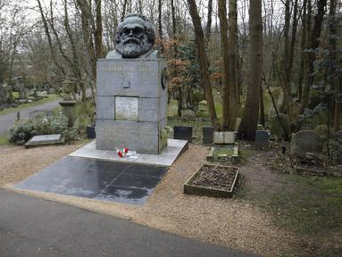 Pengunjung berjalan dekat makam filsuf ternama Jerman dan tokoh sosialisme, Karl Marx, di Pemakaman Highgate, London, Selasa (5/2). Nisan peringatan terbuat dari marmer yang menandakan persemayaman Marx dirusak oleh orang tidak dikenal. (Tolga AKMEN/AFP)
