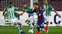 Striker Barcelona, Lionel Messi, berusaha melewati pemain Real Betis pada laga La Liga di Stadion Camp Nou, Sabtu (7/11/2020). Barca menang dengan skor 5-2.(AP/Joan Monfort)