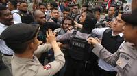 Polisi terlibat aksi saling dorong saat berusaha membubarkan massa FRI-WP dan AMP di Jalan Medan Merdeka Barat, Jakarta, Selasa (15/8). Kericuhan terjadi akibat polisi melarang aksi di depan Istana Negara. (Liputan6.com/Immanuel Antonius)