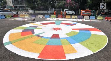 Petugas Prasarana dan Sarana Umum (PPSU) Kelurahan Pegangsaan saat menyelesaikan pembuatan logo Asian Games 2018 di Jalan Penataran atau Simpang Tugu Proklamasi, Jakarta, Rabu (25/7).  (Merdeka.com/Iqbal S. Nugroho)