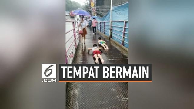 Dua orang bocah Filipina jadikan jembatan penyeberangan orang menjadi tempat bermain perosotan. Mereka memenfaatkan kondisi JPO yang licin karena hujan.