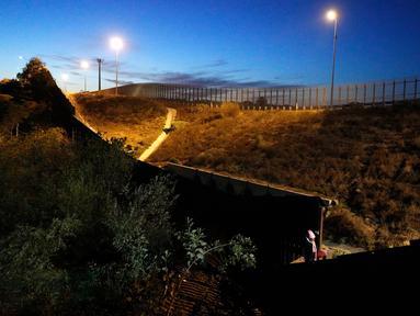 Seorang imigran memanjat pagar perbatasan ke sisi AS, dari Playas de Tijuana, Meksiko (3/12). Ribuan imigran dari Amerika Tengah melakukan perjalanan menuju Amerika Serikat dalam rombongan atau karavan. (AP Photo/Rebecca Blackwell)
