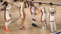 Pemain Miami Heat, Jimmy Butler (tengah) bersama rekan-rekan setimnya setelah kemenangan atas Milwaukee Bucks di  the Field House at ESPN Wide World, Kamis (3/9/2020) pagi WIB. (Mike Ehrmann/Getty Images via AFP)
