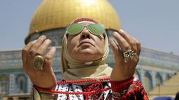 Seorang wanita Palestina berdoa di depan Kubah Shakhrah yang berada di tengah kompleks Masjid Al Aqsa, Yerusalem (8/6). Mereka memanfaatkan hari Jumat terakhir di bulan Ramadan untuk berdoa dan salat berjemaah di Masjid Al Aqsa. (AP/Mahmoud Illean)