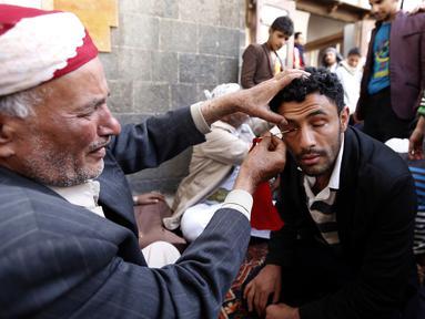 Seorang pria saat kelopak matanya dirias dengan kohl atau celak di  Masjid Agun di kota tua ibukota Sanaa, Yama, (19/5). Pemakaian kohl atau celak diyakini muslim Yaman mampu membersihkan dan melindungi mata dari penyakit. (AFP Photo/Mohammed Huvais)