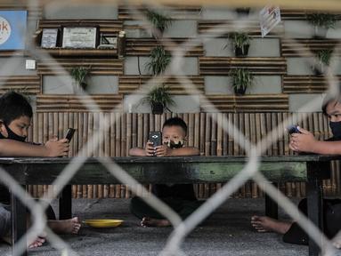 Sejumlah siswa menggunakan jaringan JakWiFi saat mengikuti kegiatan PJJ di Rumah Diskusi RT 007/008 Cipinang Besar Utara, Jakarta, Selasa (8/9/2020). Pemerintah Provinsi DKI Jakarta mengklaim telah menyediakan 4.956 titik jaringan JakWiFi di lima wilayah administrasi. (merdeka.com/Iqbal S. Nugroho)