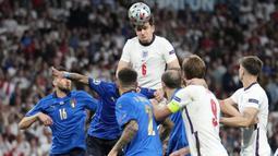 Bek Timnas Inggris,  Harry Maguire, menyundul bola saat melawan Italia pada laga final Euro 2020 di Stadion Wembley, London hari Senin (12/07/2021). (Foto: AP/(Frank Augstein,Pool)