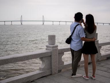 Pasangan mengabadikan Jembatan Hong Kong-Zhuhai-Makau (HKZM) di Zhuha (22/10). Jembatan laut terpanjang di dunia yang menghubungkan Hong Kong, Makau, dan daratan Cina ini akan dibuka untuk lalu lintas pada 24 Oktober 2018. (AFP Photo/Fred Dufour)