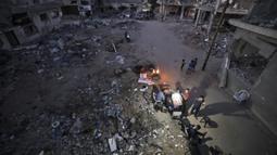 Warga Palestina berkumpul dekat reruntuhan bangunan yang hancur selama konflik antara Hamas dan Israel pada Mei 2021 di Beit Hanun, Jalur Gaza, Senin (7/6/2021). Hamas dan Israel gencatan senjata setelah perang selama 11 hari. (MAHMUD HAMS/AFP)