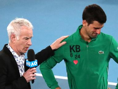 Reaksi Novak Djokovic saat diwawancarai tentang kematian Kobe Bryant usai mengalahkan Milos Raonic pada perempat final Australia Terbuka di Melbourne, Selasa (28/1/2020). Djokovic mengenakan jaket dengan inisial dan nomor punggung Kobe Bryant untuk menghormati temannya itu. (AP Photo/Dita Alangkara)