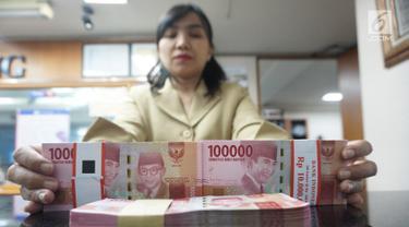 Teller menunjukkan mata uang rupiah di penukaran uang di Jakarta, Rabu (10/7/2019). Nilai tukar rupiah terhadap dolar Amerika Serikat (AS) ditutup stagnan di perdagangan pasar spot hari ini di angka Rp 14.125. (Liputan6.com/Angga Yuniar)