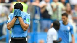 Striker Uruguay, Luis Suarez bersedih sambil menutupi wajah dengan jersey setelah kalah atas Prancis pada perempat final Piala Dunia 2018 di Nizhny Novgorod Stadium, Jumat (6/7). Timnas Uruguay tersingkir usai ditumbangkan Prancis 0-2 . (AP/Hassan Ammar)