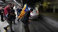 Pengunjuk rasa membawa bendera Catalonia melompat ke jalur kereta api di Stasiun Sants di Barcelona (8/11). Pengunjuk rasa memblokir jalan dan jalur kereta api setelah para pemimpin separatis ditahan di Madrid. (AFP Photo/Lluis Gene)