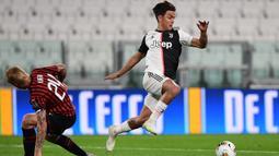 Penyerang Juventus, Paulo Dybala, berebut bola dengan pemain AC Milan pada laga leg kedua semifinal Coppa Italia di Allianz Stadium, Sabtu (13/6/2020) dini hari WIB. Juventus lolos ke final usai bermain imbang 0-0 atas AC Milan. (AFP/Miguel Medina)