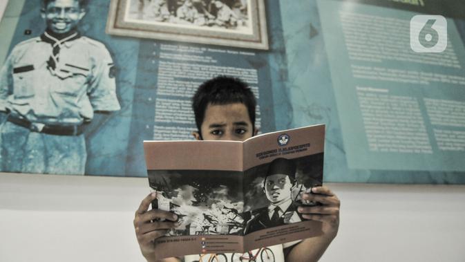 Seorang anak membaca buku panduan sejarah saat mengunjungi Museum Sumpah Pemuda, Jakarta, Rabu (28/10/2020). Libur cuti bersama dimanfaatkan untuk mengajak anak-anak mengenal sejarah lahirnya Sumpah Pemuda agar memahami jejak perjuangan pahlawan sejak dini. (merdeka.com/Iqbal Nugroho)