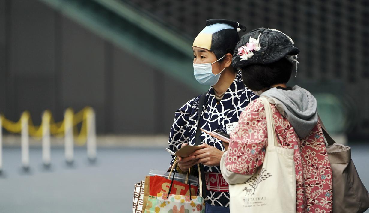 Seseorang memakai masker untuk membantu mencegah penyebaran virus corona memakai wig samurai di Tokyo, Selasa (6/4/2021). Ibukota Jepang mengonfirmasi lebih dari 390 kasus virus korona baru pada hari Selasa. (AP Photo/Eugene Hoshiko)