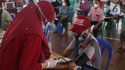 Petugas medis mengecek kesehatan seorang lansia sebelum melakukan vaksinasi Covid-19 di Gor Total Persada, Kota Tangerang, Selasa (8/6/2021). Vaksinasi tersebut untuk melindungi mereka dari Covid-19 yang tengah mewabah. (Liputan6.com/Angga Yuniar)