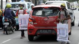 Pedagang menawarkan kalender tahun 2021 kepada pengguna jalan di perempatan Pondok Pinang, Kebayoran, Jakarta Selatan, Senin (7/12/2020). Jelang pergantian tahun, sejumlah pedangang mulai menjajakan kalender tahun 2021 dengan harga Rp 20 ribu-Rp 40 ribu tergantung ukuran. (merdeka.com/Dwi Narwoko)