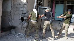 Tiga anggota pasukan Irak mengeluarkan jenazah militan ISIS dari sebuah bangunan yang akan dimakamkan di Karamah, selatan Mosul, Irak, (11/11). (REUTERS/Goran Tomasevic)