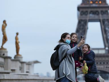 Seorang ibu dan anak-anaknya berswafoto di Lapangan Trocadero dekat Menara Eiffel di Paris, Prancis, pada 16 November 2020. Prancis pada Senin (16/11) melaporkan tambahan 506 kematian akibat virus corona COVID-19, lebih tinggi dibandingkan 302 kematian pada Minggu (15/11). (Xinhua/Gao Jing)