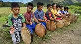 Sejumlah anak laki-laki memainkan rebana tradisional saat mengambil bagian dalam tari Rapa'i Geleng di sepanjang sawah di desa ekowisata Nusa, Lhoknga, Provinsi Aceh, 26 September 2021. Rapa'i Geleng adalah tarian yang berasal dari Aceh bagian selatan tepatnya Manggeng. (CHAIDEER MAHYUDDIN/AFP)