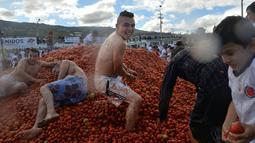Peserta mengmbil tomat saat Festival Tomatina di Sutamarchan, Boyaca, Kolombia, Minggu (2/6/2019). Festival Tomatina ini sudah memasuki tahun ke-10. (Diana SANCHEZ/AFP)