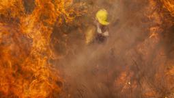 Petugas pemadam kebakaran memadamkan api di Capilla del Monte, Cordoba, Argentina (15/10/2020). Kebakaran diperburuk oleh kekeringan ekstensif yang dialami wilayah tersebut. (AP Photo/Mario Tizon)