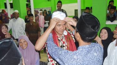 Seorang santri di Ponpes El Bayan, Majenang, Cilacap, memakaikan kopyah kepada Gubernur Jawa Tengah, Ganjar Pranowo. (Foto: Liputan6.com/Muhamad Ridlo)