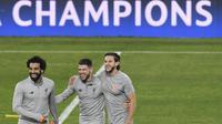Pemain Liverpool, Mohamed Salah, Alberto Moreno dan Adam Lallana, tertawa saat sesi latihan jelang laga Liga Champions di Stadion Ramon Sanchez Pizjuan, Senin (20/17/2018). Liverpool akan berhadapan dengan Sevilla.  (AFP/Cristina Quicler)