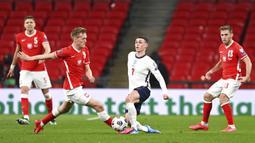 Pemain Polandia Karol Swiderski (kedua kiri) memperebutkan bola dengan pemain Inggris Phil Foden pada pertandingan Grup I kualifikasi Piala Dunia 2022 di Stadion Wembley, London, Inggris, Rabu (31/3/2021). Inggris menang dengan skor 2-1. (Andy Rain/Pool via AP)