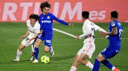 Pemain Real Madrid, Alvaro Odriozola, berebut bola dengan pemain Getafe, Marc Cucurella, pada laga Liga Spanyol di Stadion Alfonso Perez, Senin (19/4/2021). Kedua tim bermain imbang 0-0. (Photo by PIERRE-PHILIPPE MARCOU / AFP)