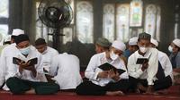 Para siswa mengenakan masker untuk membantu mengekang penyebaran COVID-19 saat membaca kitab suci Alquran di Masjid Attaqwa, Bekasi, Jawa Barat, Selasa (4/5/2021). Selama Ramadhan, umat muslim menahan diri dari makan, minum, merokok dan seks dari subuh hingga maghrib. (AP Photo/Achmad Ibrahim)