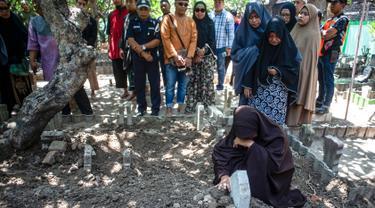 Bibi (kanan bawah) dari penyelam Syachrul Anto yang meninggal dunia kala melakukan evakuasi jatuhnya pesawat Lion Air PK-LQP, berdoa saat pemakaman di Surabaya, Jawa Timur, Sabtu (3/11). Syachrul Anto meninggal karena dekompresi. (JUNI KRISWANTO/AFP)