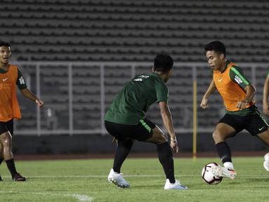 Pemain Timnas Indonesia U-23, Nurhidayat Haris, berebut bola saat berlatih di Stadion Madya, Jakarta, Selasa (23/7). Latihan ini merupakan persiapan jelang SEA Games 2019. (Bola.com/Yoppy Renato)