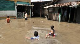 Anak- anak bermain saat banjir menggenangi kawasan Rawa Terate, Cakung Jakarta, Rabu (30/1). Ratusan rumah di RT 016/004 dan RT 010/005 Kelurahan Rawa Terate, terendam banjir sejak dini hari. (merdeka.com/Iqbal S. Nugroho)