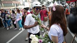 Anggota TKN Milenial Jokowi-Ma'ruf membagikan bunga kepada pengunjung car free day dalam kegiatan tabur bunga di Bundaran HI, Jakarta, Minggu (28/4/2019). Mereka mengajak masyarakat untuk ikut mengungkapkan duka atas meninggalnya 272 petugas KPPS dalam Pemilu 2019. (Liputan6.com/Faizal Fanani)