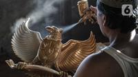 Perajin menyelesaikan proses pewarnaan patung Garuda Pancasila di industri rumahan di Jalan Bali Raya, Jakarta, Kamis (1/10/2020). Perajin menjual patung Garuda Pancasila dengan harga yang dijual berkisar Rp100 ribu-Rp125 ribu per buah. (merdeka.com/Iqbal S. Nugroho)