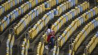 Pendukung Peru melewati kursi kosong Stadion Maracana jelang laga melawan Bolivia pada Copa America 2019, Senin (18/6/2018). (AFP/Mauro Pimentel)