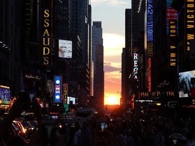 Matahari terbenam di antara pencakar langit, sejajar tepat dengan jalan, ketika fenomena Manhattanhenge di 42nd street di Times Square, New York City, Kamis (12/7). Fenomena ini hanya terjadi selama beberapa hari dalam setahun. (AFP/TIMOTHY A. CLARY)