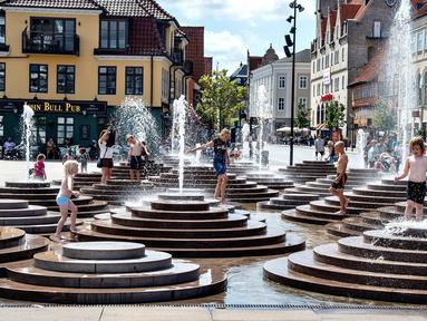 Anak-anak mendinginkan diri dengan bermain di air mancur saat gelombang panas menerjang Eropa di Toldbod Plads, Aalborg, Denmark, Rabu (24/7/2019). Eropa Barat dilanda gelombang panas yang hebat minggu ini. (Henning Bagger/Ritzau Scanpix via AP)