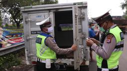 Petugas kepolisian melakukan pengecekan terhadap mobil box yang keluar Tol Merak, Banten, Senin (18/5/2020). Pemeriksaan (check point) tersebut terkait larangan mudik guna penyekatan atau memeriksa kemungkinan pemudik yang akan keluar dari wilayah Jabodetabek. (Liputan6.com/Angga Yuniar)