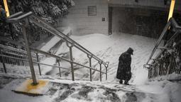 Seorang perempuan berjalan dengan hati-hati menuruni tangga ke stasiun kereta bawah tanah Columbus Circle saat badai salju melanda New York, Senin, (1/2/2021). Badai salju menyebabkan timbunan salju setinggi satu kaki di sepanjang wilayah pesisir timur AS, termasuk New York. (AP Photo/Wong Maye-E)