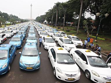 Ratusan armada taksi parkir di sepanjang silang Monas, Jakarta, (14/3). Mereka merasa dirugikan dengan banyaknya tranportasi berplat hitam yang berbasis online tersebut. (Liputan6.com/Immanuel Antonius)