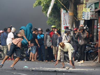 Massa melempar batu ke arah aparat keamanan saat terjadi bentrok di kawasan Slipi, Jakarta Barat, Rabu (22/5/2019). Kerusuhan ini buntut aksi 22 Mei menolak hasil Pilpres 2019 yang diumumkan oleh KPU. (Liputan6.com/Gempur Muhammad Surya)