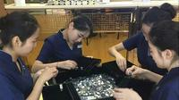 Petugas toko perhiasan tengah menghitung uang koin dari Liang untuk membeli cincin. (Shanghaiist)