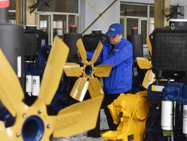 Pekerja mengecek mesin buldoser di sebuah pabrik di Zhangjiakou di provinsi Hebei, China Utara (10/4). Buldoser adalah jenis peralatan konstruksi biasa disebut alat berat bertipe traktor menggunakan Track/rantai serta dilengkapi dengan pisau yang terletak di depan. (AFP Photo/Str/China Out)
