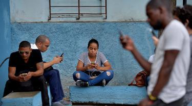 Orang-orang menggunakan ponsel mereka untuk terhubung ke internet melalui WiFi di sebuah taman di Havana, Rabu (5/12). Pemerintah Kuba mengumumkan bahwa masyarakat bisa mengakses internet secara bebas di ponsel mereka mulai Kamis ini. (YAMIL LAGE/AFP)