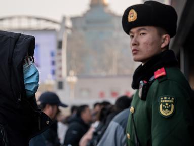 Seorang pria mengenakan masker penutup mulut setibanya di stasiun kereta api Beijing untuk mudik Tahun Baru Imlek pada Selasa (21/1/2020). Virus mirip SARS yang menyebar ke seluruh wilayah China dan mencapai tiga negara Asia ternyata dapat menular dari satu orang ke orang lain. (NICOLAS ASFOURI/AFP)